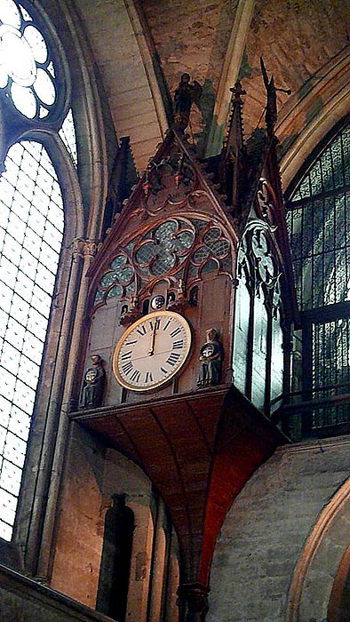 An ornate clock, with animated chimes, inside the Cathedral of Reims, located near the doorway through which only the Canons would enter to fulfill their prayer duties.