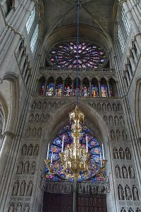 Towards the back of the Reims Cathedral, looking up at the stained glass windows set into the front facade.