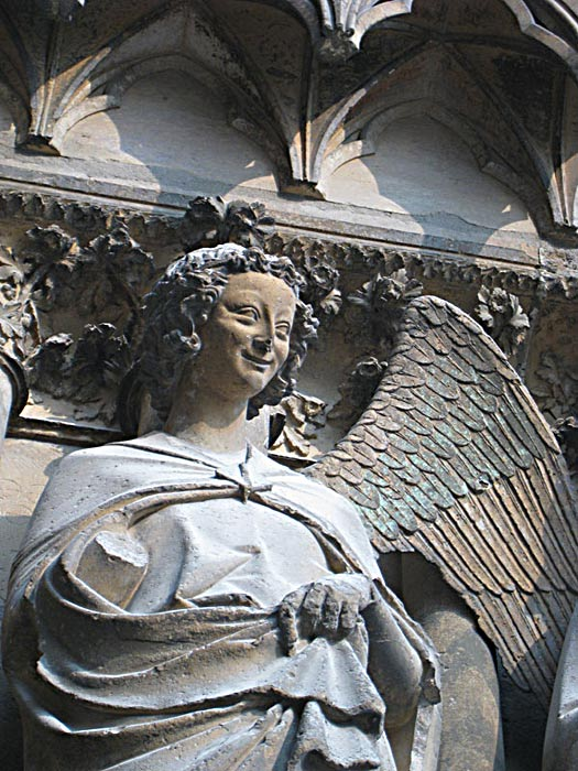 """Detail of one of the """"smiling angels"""" on the facade of the Reims Cathedral."""