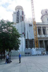 Filming in front of the repair work being done of the church of Saint Sulpice.