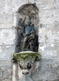 Close up of the statue of De La Salle in a wall niche above the entrance of a former Lasallian school location in Laon, France.